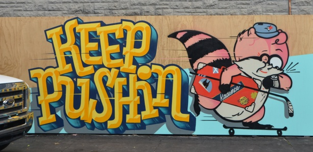 large yellow letters that say keep Pushin, on a mural with a pink raccoon wearing a blue jays baseball cap, looking at a wrist watch with a dollar sign on the face,