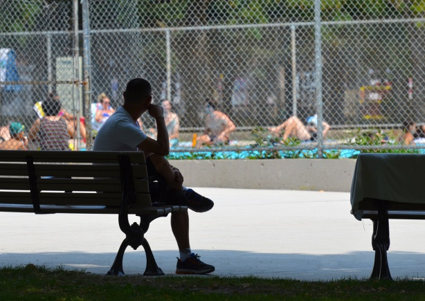 a man site on a bench, in silhouette, with an outdoor pool in the background with people sitting around it