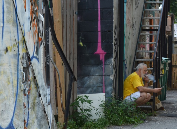 a man with a yellow t shirt sits on a back step in an alley and smokes a cigarette
