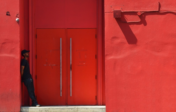 a man leans against the wall in a doorway of a building, the building is all red including the doors