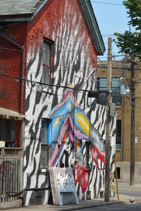 an old mattress and white head board lean against the wall, outside, of a house that has a large mural painted on it of legs with feet in bright red high heeled shoes