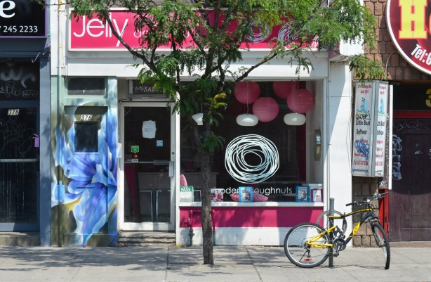 front window of Jelly, a modern doughnut store on Queen West, small tree in front of it