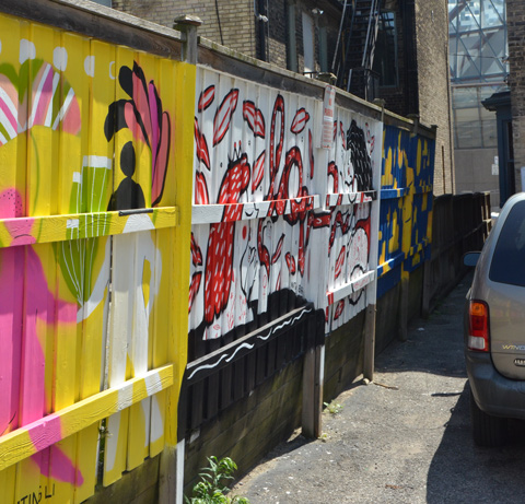 a gold coloured van is parked beside a fence that has three murals painted on it, in an alley