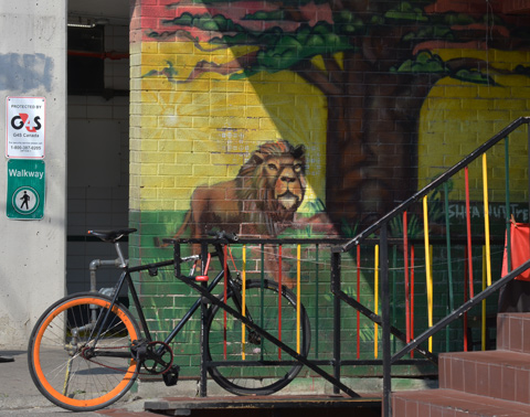 a bike is parked beside a mural with a lion on it