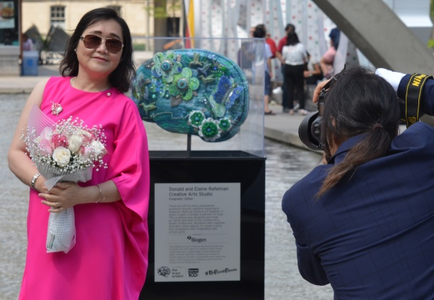 woman in a bright pink dress, holding a bouquet of flowers poses beside a brain artwork at Nathan Phillips Square while a man in a blue suit takes her picture