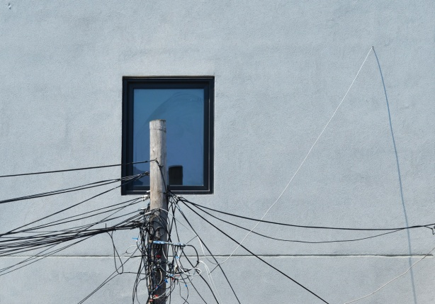 a utility pole with a lot of wires coming out from the top of it in front of a pale grey wall with a window that is reflecting the blue sky
