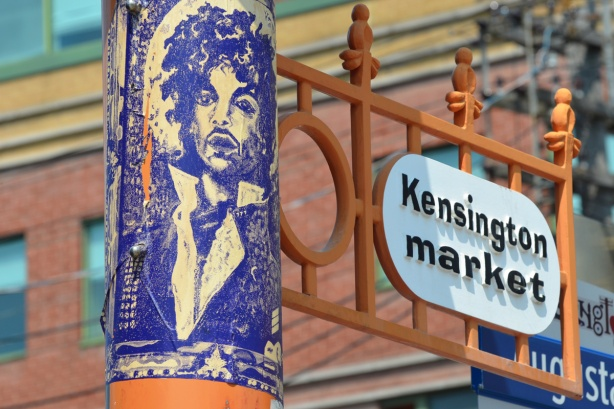 a poster with the picture of Prince on it, on a pole, up high beside sign saying Kensington Market