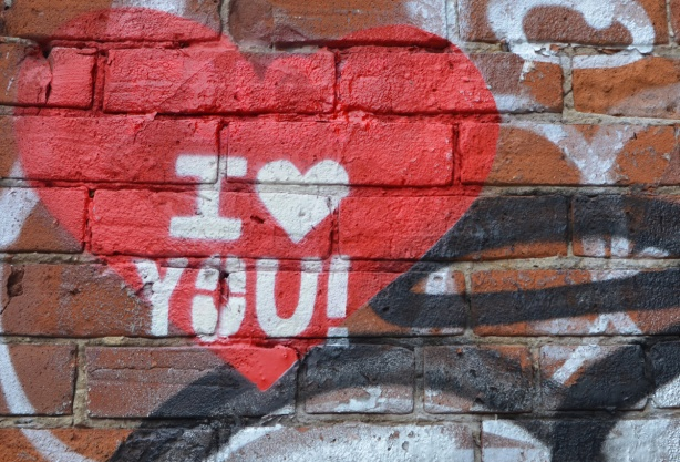 graffiti on a brick wall, red heart with words I love you, instead of the word love there is a white heart