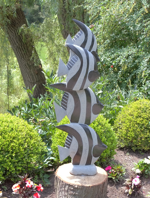 a sculpture titled Shoal, 4 striped fish, one on top of the other, sculpture with flowers in front and greenery behind, Edwards Gardens
