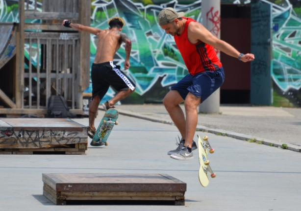 two young men skate boarding, both jumping at the same time, arm in air,