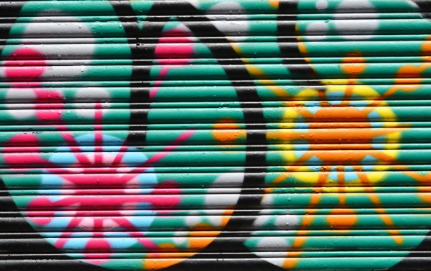 part of a painting on a metal garage door of two starburst shapes, one in pink and one in yellow
