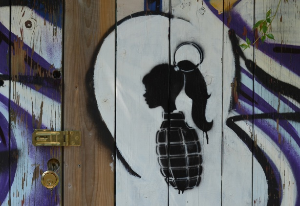 small black stencil of a hand grenade on a fence, the top of the grenade is a girl's head in profile, with a ponytail