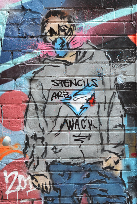 street art painting of a street artist in grey hoody and mask, hoody has Toronto blue jays logo, but someone has used black marker to write words on hoody say Stencils are wack