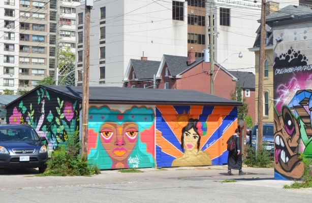 An alley way with a double garage and a car parked beside it, high rise buildings behind it, a young man walking past it. Each door is painted with a mural of a woman's head, one by Desire Betty (dbetty13) and the other by Sarah Gilmore, or toest. On the side of the garage is another mural, this one by nightarcade, Sarah Cannon,