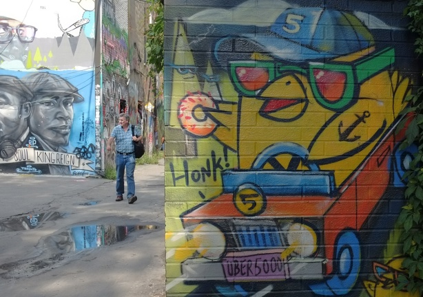 A man avoids the puddles in the lane as he walks past an uber5000 mural of a yellow birdie with a donut, birdie is driving a little orange car