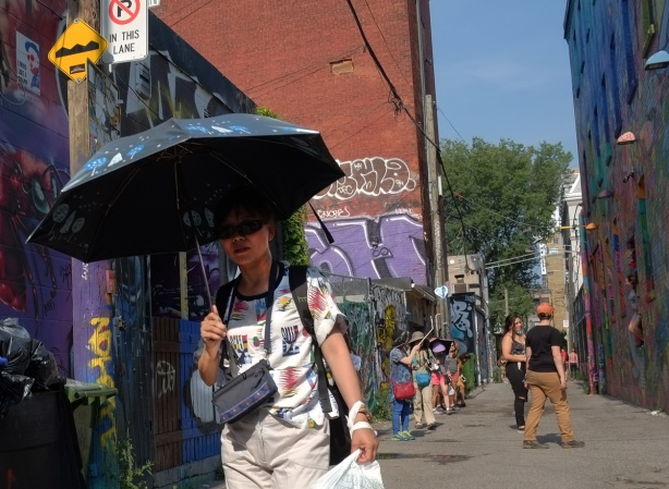 a woman carries an open blue umbrella on a sunny day as she walks down Graffiti Alley