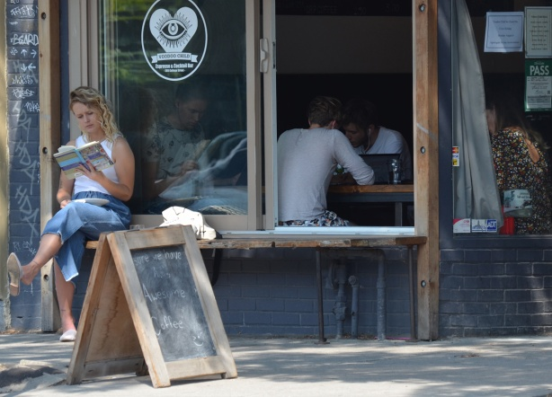 a woman sits outside a coffee shop reading a book. the window of the coffee shop is open and there are 4 people sitting inside