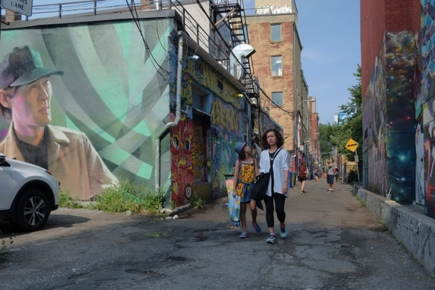 a mother and daughter walk down Graffiti Alley, past a lrge mural of a young man by Janus