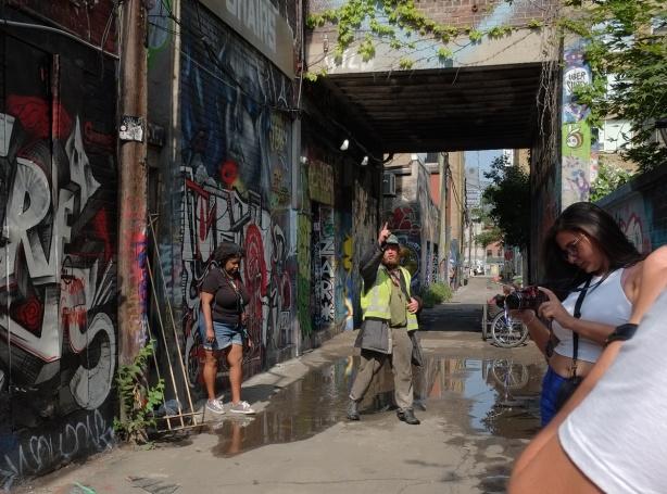 a man in a yellow vest is talking in Graffiti Alley