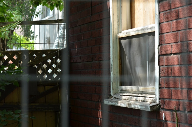 behind a metal fence, an old house with a boarded up window