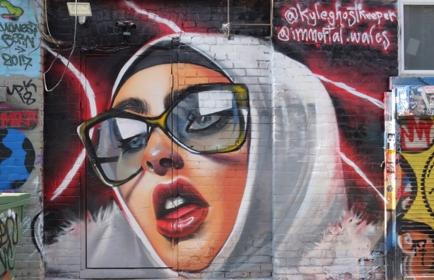 woman wearing a white head scarf and large glasses, with red lips