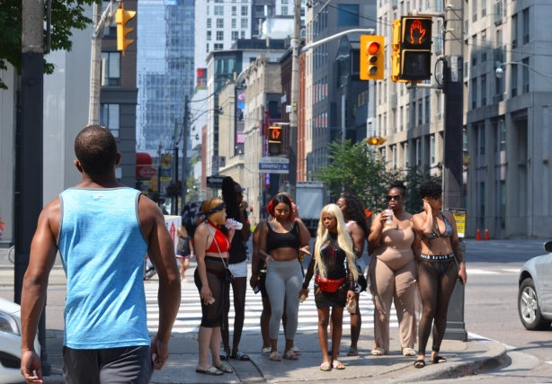 a group of scantily clad black women wait to cross University Ave
