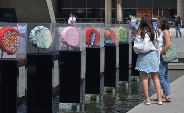 two young woman are standing beside a row of artwork, brain shaped, each in a plexiglass container, standing in the water of the fountain at Nathan Phillips Square, 7 brain sculptures, all decorated by different artists, part of the brain project in support of Baycrest