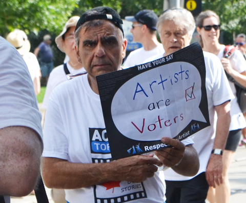 labour Day parade on Queen St West, ACTRA member male, carrying sign that says Artists are Voters,