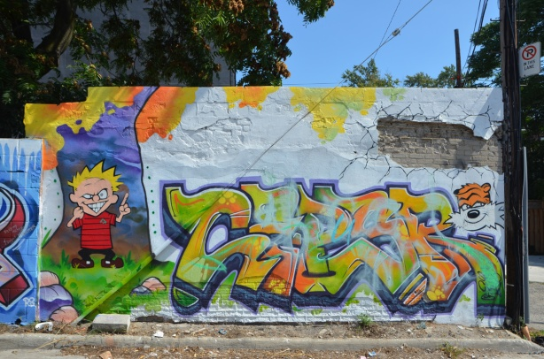 in a popart mural by Matt Gondek and Jackson, in an alley, calvin and hobbes and some text in between