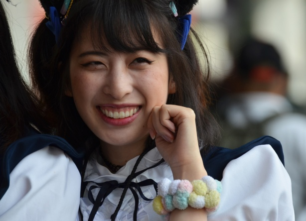 asian woman in navy and white frilly anime french maid costumes, with hair tied up with bows, pompom bracelet on
