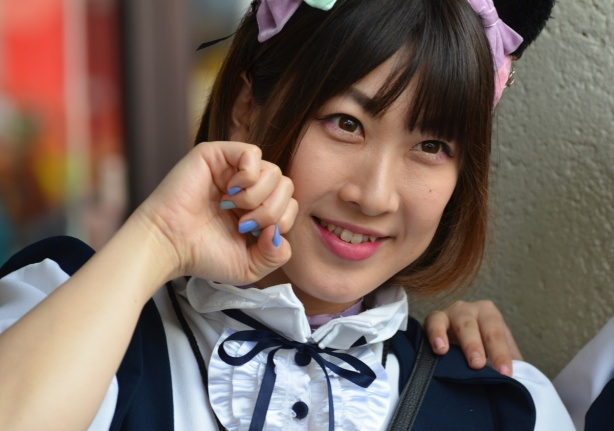 asian woman in navy and white frilly anime french maid costumes, with hair tied up with pink and green bows, blue nail polish
