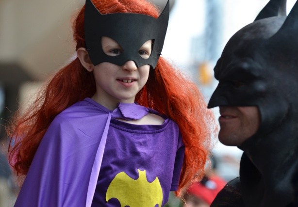 child in long red wig and batman mask, also purple batman costume with a yellow bat symbol, Batman is in the right of the pic