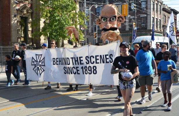labour Day parade on Queen St West, IATSE local 58, banner, with the words Behind the scenes since 1898, some people walking including a young woman carrying a bag of buttons that she's handing out.