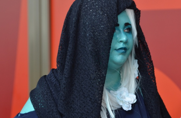 woman in turquoise face paint, dark blue veil and a white frilly collar and white hair