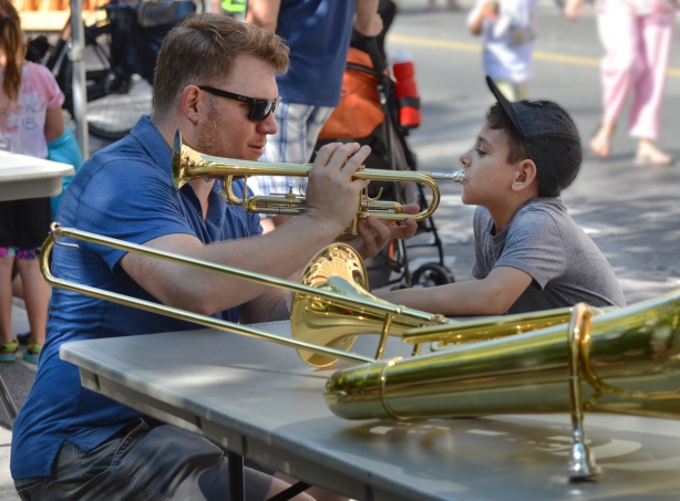 a man teaches a boy to blow a trombone, outdoors, activity on the sidewalk during Open Streets