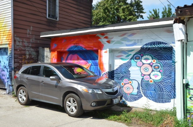 a grey car is parked in front of a double garage, each door has a mural painted on it