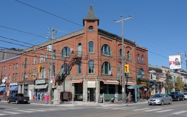 three storey red brick building on corner of college and dovercourt, northeast corner, stores on the lower leve, traffic lights, utility poles and streetcar wires
