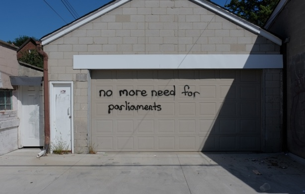 a beige garage door with the words no more need for parliaments written on it