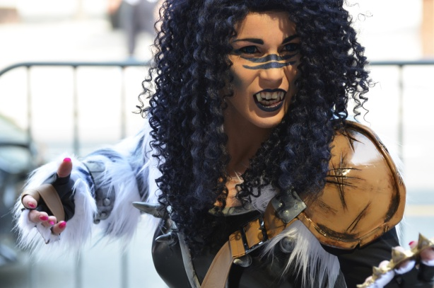 a woman in costume, long curly black hair, fangs, black lips, claws and fur on hands,
