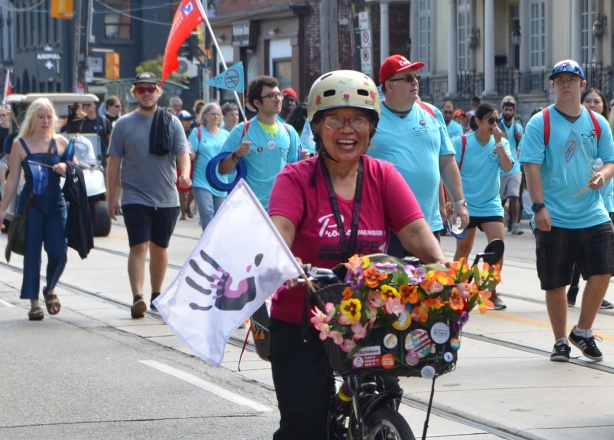 labour Day parade on Queen St West, woman in pink t-shirt riding a bike in front of walkers in the parade