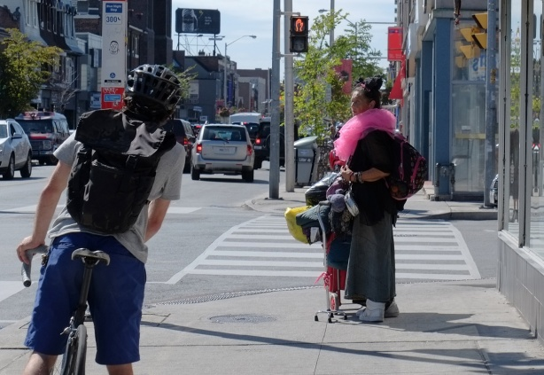 the back of a cyclist stopped at the side of a street by a bus stop, and traffic light, a woman stands on the sidewalk with a large puffy pink scarf around her neck and a lot of belongings with her