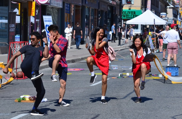 four young people dancing in the street, two male and two female.