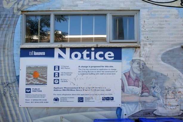 blue and white city of toronto development notice sign on the side of a building, under a window, beside a mural of a baker in chefs hat and white apron icing a three layer wedding cake