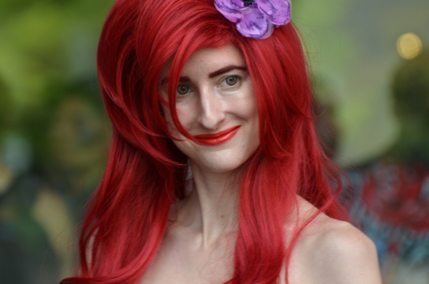 a woman dressed up as Ariel, the Disney mermaid, long red hair and a purple flower in her head