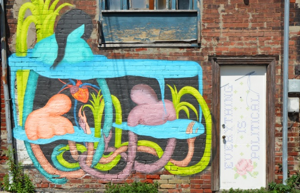a white door with words that say Everything is political, also a large mural painted beside the door, two figures amongst pink, yellow and pale blue curly vines and leaves, abtract