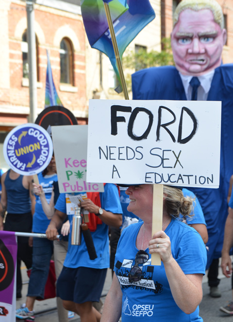 labour Day parade on Queen St West, a woman with a sign that says Ford needs a sex education, walking in front of large oversized effigy of Doug Ford