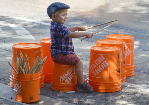 a young boy uses wooden drum sticks to bang on upturned orange plastic buckets from Home Depot, outside, activity at Open Streets