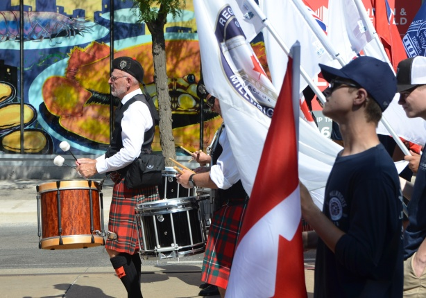 labour Day parade on Queen St West, man in tartan kilt playing drums, union members carrying flags including Canadian flag