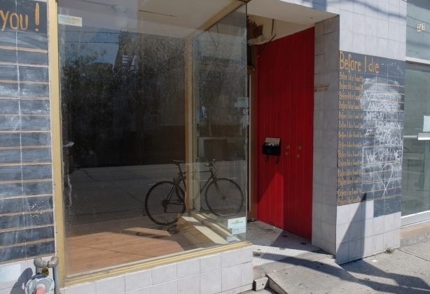 empty store front with a bike parked inside, a red wall beside the door way, dirty glass in front, reflections in the glass