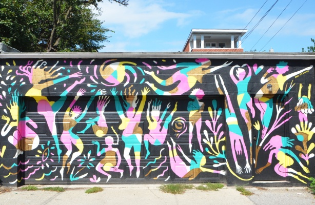 garage front covered with a mural by Erin McCluskey, black background, then figures of women in pink, yellow and pale blue, dancing, playing, flying, jumping,